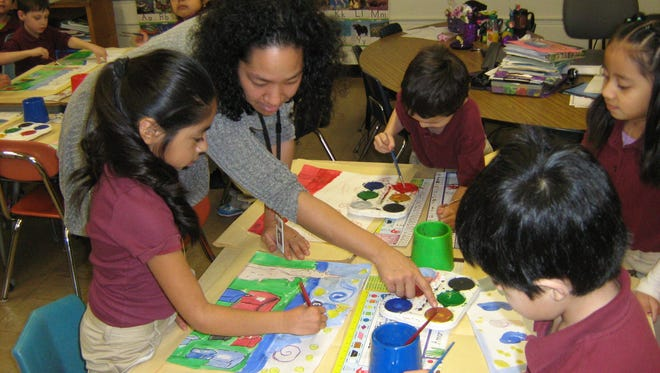 Kimberly Moore, a Bridgeton art instructor, works with enthusiastic first graders, who hope to earn a Gold Brush Award.