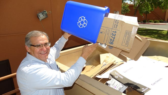 Gilbert Apodaca, director, uses one of the new blue bins to top off recyclables already collected in the huge rolloff container provided and serviced by the SCSWA.