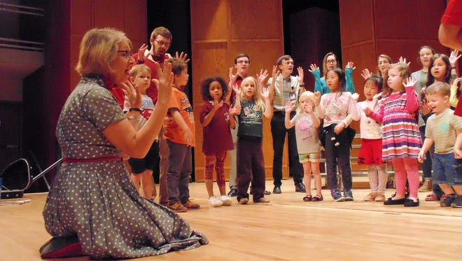 Suzanne Byrnes works with the Capital Children's Choir in preparation for a concert on Monday.
