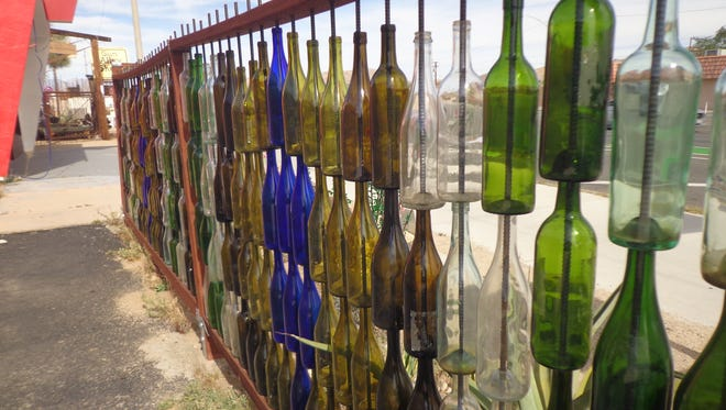 Fence stringers hold rebar threaded with drilled wine bottles.