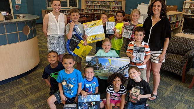 Champions for Children participants show off their new toys provided by the Portage Resale Center Youth Council. At left, standing, is Alexis Yoh  from Portage Resale Center Youth Council, and at right, standing, is Lisa Chura, Champions for Children Site Director.