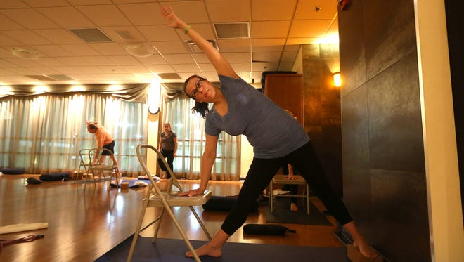 Democrat and Chronicle reporter  Victoria Freile takes part in a gentle yoga class, perfect for expecting mothers, at Midtown Athletic Club.