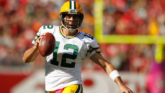Packers quarterback Aaron Rodgers runs for a first down against the 49ers.