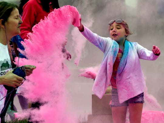 Gianna Robinson, 10, of Evansville tosses some pink-colored powder near passing runners during the Color Me Fun run/walk along West Franklin Street in Evansville during a previous Color Me Fun Run.