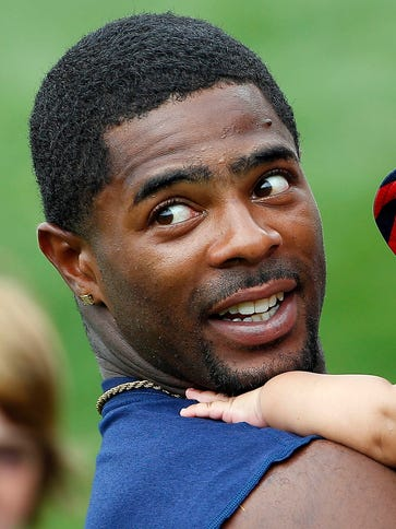 Malcolm Butler, holding  his son after practice this
