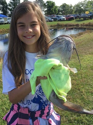 Savannah Ehrhard, 11, holds up a 2.82-pound catfish she caught Saturday at the Cross Lake Fish Hatchery during the ALBC Youth Fishing Tournament.