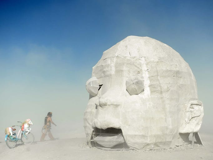 "Sam Ray visits the ""Baby Head"" art piece on the playa"