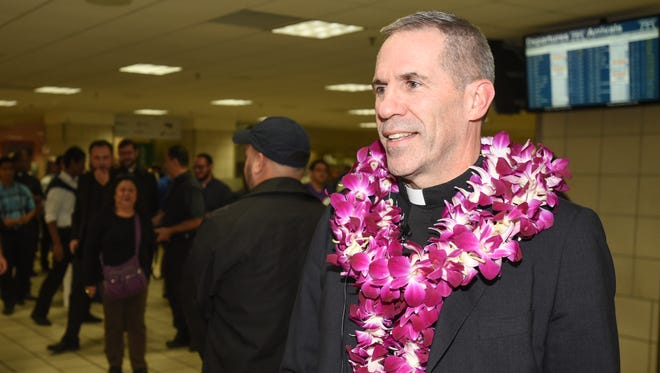 Coadjutor Archbishop Michael Jude Byrnes, speaks with Pacific Daily News reporter Haidee Eugenio, after his arrival at the A. B. Won Pat International Airport during the early morning hours of Monday, Nov. 28, 2016.