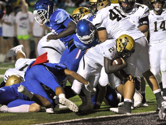 Abilene High's Niyungeko Moise carries the football over the goal line for a touchdown late in their game Friday against Cooper. Cooper won, 49-35.