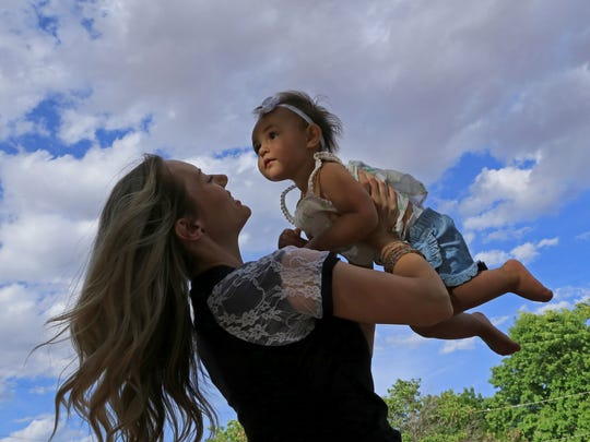 Sunlight filters through the trees at Nisson Park on May 2 in Washington City, illuminating Giselle Judd's face as she's held aloft by her mother, Chelsea.