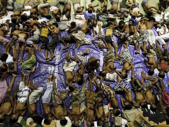 Migrants believed to be Rohingya rest inside a shelter