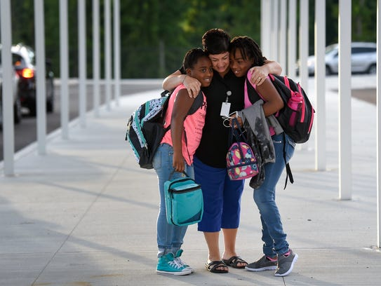 Teacher Angie Carroll greets Khyla, left, and Kayce