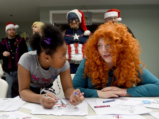 """Brittany Shade, right, portraying Merida from the movie """"Brave,"""" colored pictures with 9-year-old Destiny Aldridge on Saturday, Dec. 10, 2016. Shade, of the Central Pa. Avengers, was helping during a Christmas celebration from the LifePath Christian Ministries women and children's shelter."""