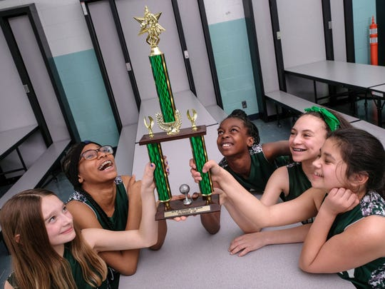Most Holy Trinity School JV girls basketball team members Julianna Izzard, left, Nasya Davis, Aniah Thomas, Kayla Roach and Olivia Torres with the 2018 St. Margaret Post Season fifth/sixth grade girls runner-up trophy at their school in Detroit on Wednesday, March 28, 2018.