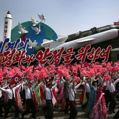 North Korean men and women wave flags and plastic flowers