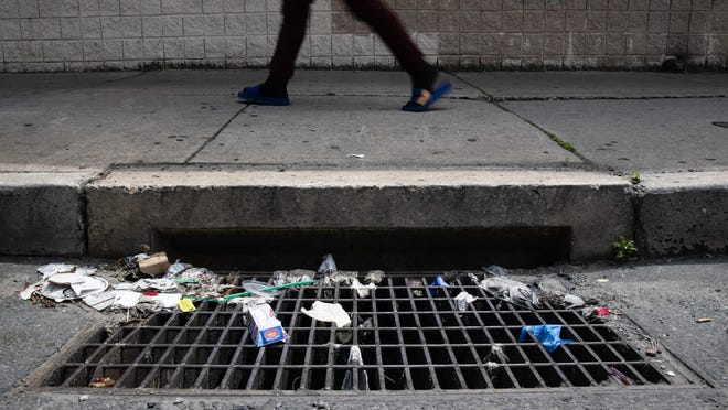 In this Monday, May 25, 2020 photo a person walks past a storm drain with discarded gloves and other trash in Philadelphia. Between mid-March, when the city's stay-at-home order was issued, and the end of April, most of the 19 sewer and storm water pumping stations in Philadelphia had experienced clogs from face masks, gloves and wipes residents had pitched into the potty, Philadelphia Mayor Jim Kenney said.