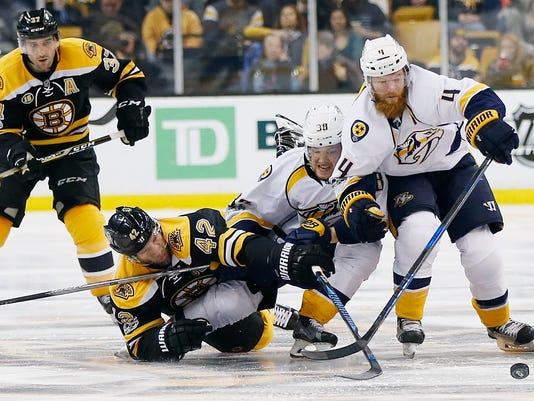Boston Bruins' David Backes (42) battles Nashville Predators' Viktor Arvidsson (38), of Sweden, and Ryan Ellis (4) during the second period of an NHL hockey game in Boston, Tuesday, March 28, 2017. (AP Photo/Michael Dwyer)