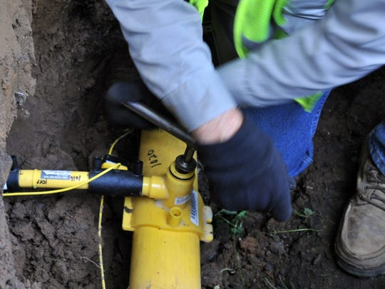Lancaster Municipal Gas employee Craig Dupler taps a line to connect a service line for a house to the main gas line Tuesday on Fair Avenue in Lancaster.
