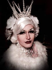 Trixi Del Mar, a drag performer, poses in an all-white costume and headpiece.