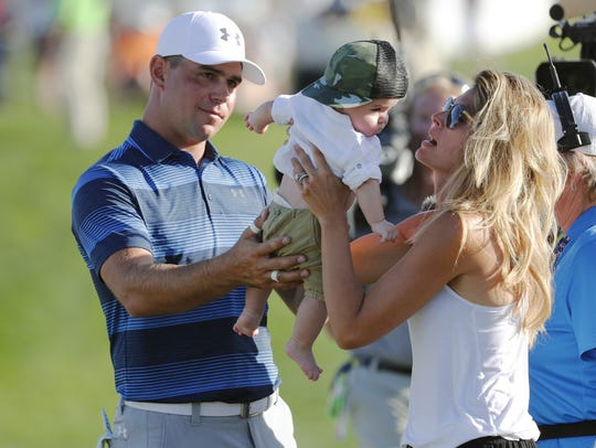 Gary Woodland hands his son, Jaxson, back to his wife,