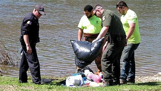 Law enforcement officers and public works employees gather some of the debris that was dumped Tuesday night in the Chemung River.