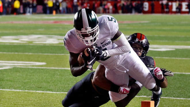 Michigan State wide receiver DeAnthony Arnett (5) dives for a touchdown as Rutgers defensive back Andre Hunt (30) cannot make a tackle during the second half of an NCAA college football game Saturday, Oct. 10, 2015, in Piscataway, N.J.
