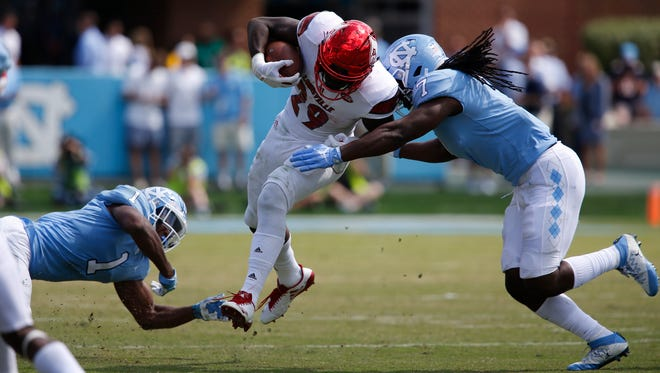Louisvilles' Malik Williams broke through two tacklers during second half action against North Carolina. Williams rushed for 149 yards. Sept. 9, 2017