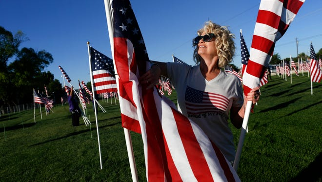 Ginger Palmer places a flag Friday for the opening of the annual Healing Fields display at the Boys & Girls Clubs of Farmington.