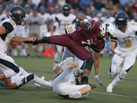 Aquinas running back Caron Robinson, center, rumbles over a swarming Victor defense to pick up a first down during the first half of their season opener at Aquinas Friday, Sept. 1, 2017. Robinson was an All-Greater Rochester choice in 2017.