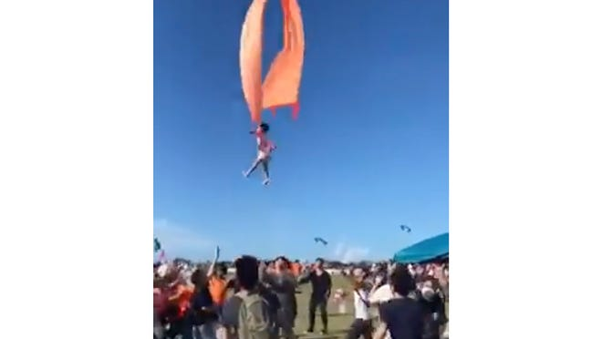 In this image made from video, a 3-year-old girl is lifted into the air by a large kite during a kite festival in Hsinchu, northern Taiwan, on Sunday. The wind slowed down and the girl was safely recovered by people on the ground.