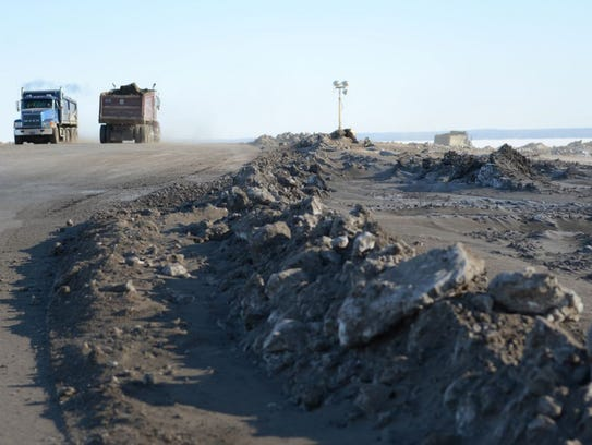 Dump trucks transport fill onto Renard Island last