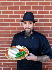 Chef-owner AJ Servidio, holds a plate with turkey and