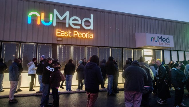 Dozens of customers wait in line as the sun rises Wednesday, Jan. 1, 2020 outside the nuMed marijuana dispensary in East Peoria, the first day of legal recreational marijuana sales in Illinois.