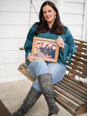 Kelley Stanley sits on the porch of her Chillicothe, Ohio, home with a picture of her children and fiancé Marcus Grubb.