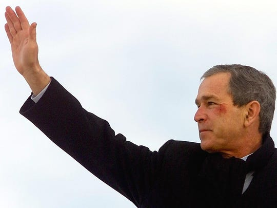 President George W. Bush waves from the steps of Air