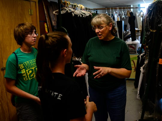 Beth Wilton, president of the band booster club the Band Aides, helps Narissa Conklin with her uniform.