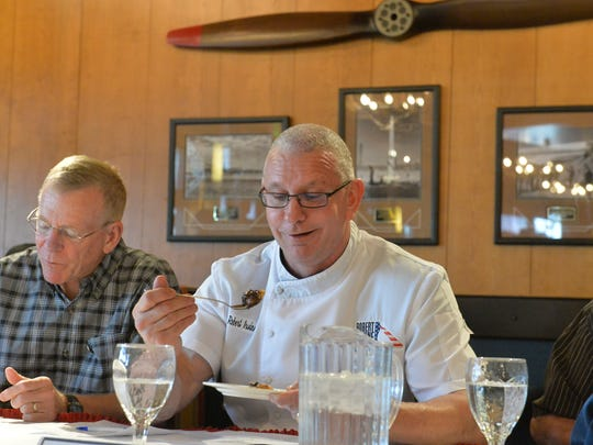 Celebrity Chef Robert Irvine, right, reacts to a good bite as Great Falls Mayor Bob Kelly, left, makes notes during judging at the Air Force missile chef cooking competition at Malmstrom.