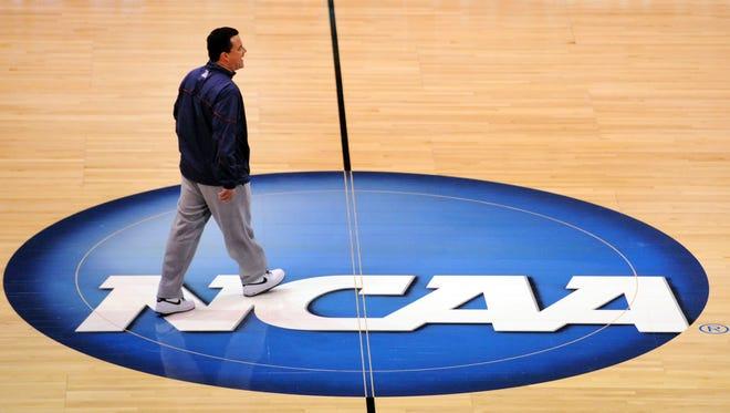 Embattled Arizona men's basketball coach Sean Miller walks across the court during a practice before an NCAA Tournament game.