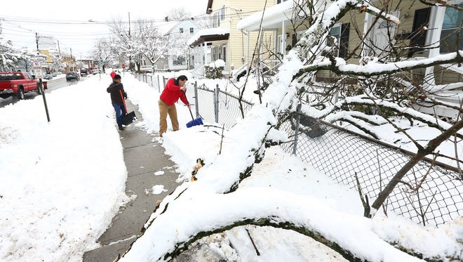 Benito Solis of Morristown shovels his walk after a tree snapped and landed on his home. Residents and business owners in Morristown dig out the morning after a nor'easter dumped over a foot and a half of snow around Morris County. March 8, 2018.  Morristown, NJ.