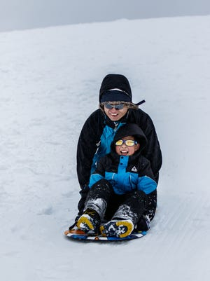 David Chang and his son Steven, 8, of Brookfield speed down the sledding hill at Mitchell Park on Sunday, April 15, 2018. A weekend storm covered the area with ice and snow luring residents outside to play.