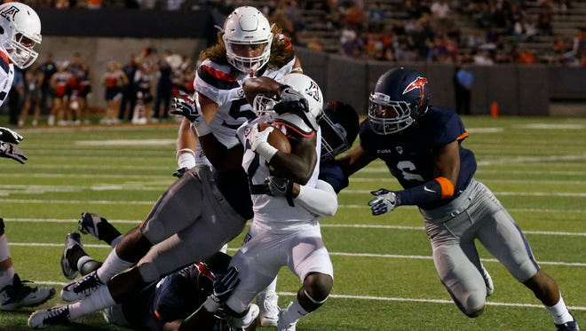 Arizona running back Nick Wilson is brought down by a swarm of UTEP defensive players during first quarter action in the Sun Bowl Friday night. The Wildcats took a 35-9 lead into the half.