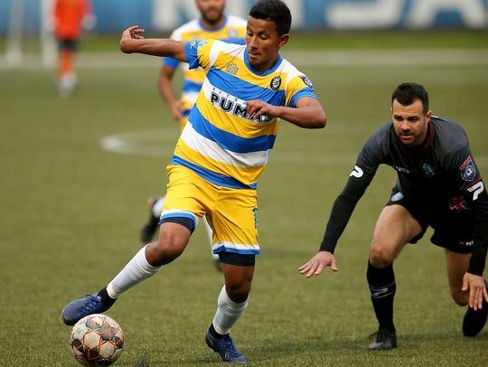 Kitsap Pumas midfielder Alex Hernandez dribbles around