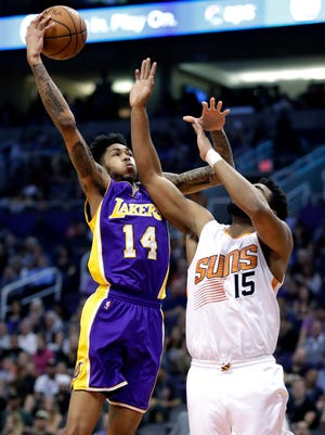 Los Angeles Lakers forward Brandon Ingram (14) shoots over Phoenix Suns forward Alan Williams (15) during the first half of an NBA basketball game, Thursday, March 9, 2017, in Phoenix.