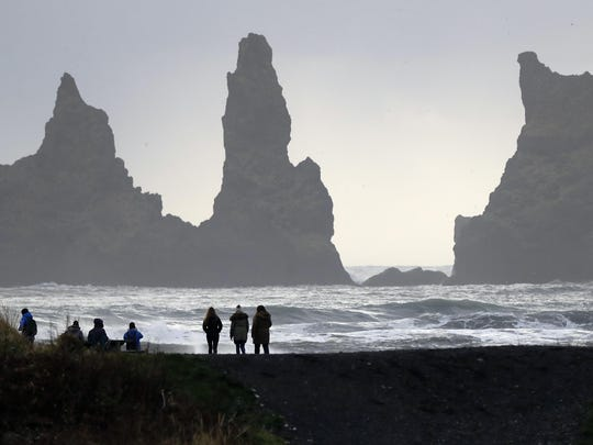 People walk on the black sanded beach in Vik, Iceland, near the Volcano Katla last month. Scientists say Katla is long overdue to erupt. When it blows, nearby residents may have 15 minutes before they are enveloped in pitch black ash.
