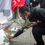 A foreigner places an olive branch at the scene after a suicide attack explosion in Istanbul on Istiklal Street on March 20, 2016. The attack occurred March 19, 2016. Five people died, including the suicide bomber.
