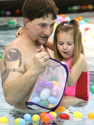 Even with Dad Shaun Davis assistance, Kaylie Davis, age 4, still has to concentrate to snatch bobbing plastic eggs from the surface of the pool at the Howell Aquatic Center Saturday during the Underwater Easter Egg Hunt.