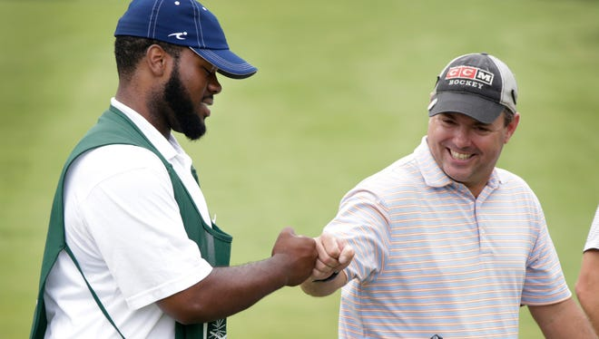 Cass Tech's Jared Ingram 18, of Detroit caddies at the Country Club of Detroit on Friday July 21, 2017 in Grosse Pointe Farms. Ingram, left, gets a fist-bump from Scott Lindsay of Grosse Pointe Park after Linsday sank a 20-foot putt for eagle on the seventh hole. Ingram has earned the Evans Scholarship, a full ride to Michigan State in the fall.