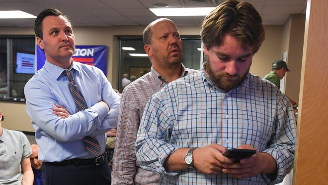 Dan Hamilton, left, Republican candidate for South Carolina 4th Congressional District watches election results at his campaign headquarters in Greenville with campaign official Walter Whetsell, center, as campaign manager Logan McVay checks results on his phone Tuesday, June 12, 2018.