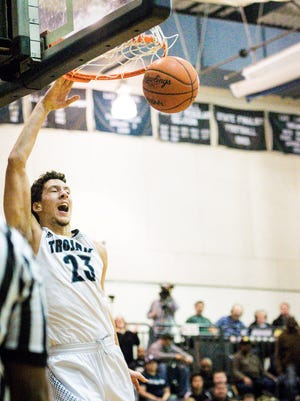 Brandon Johns of East Lansing slams the ball home to give the Trojans a 67-63 lead with 21 seconds left in their game Friday January 13, 2017 in East Lansing.