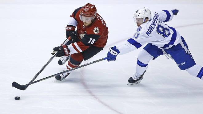 Arizona Coyotes center Max Domi (16) tries to get the puck past Tampa Bay Lightning center Jonathan Marchessault (81)  during the first period of their NHL game Saturday, March 19, 2016 in Glendale, Ariz.